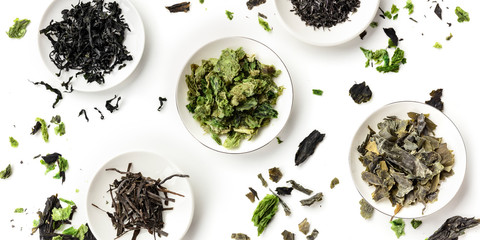 A panoramic overhead shot of a variety of dry seaweed, sea vegetables, on a white background Wall mural