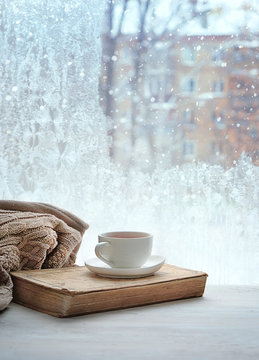 tea cup, book and sweater on background of winter window. concept of home comfort in cold snowy weather. copy space. shallow depth. close up. soft selective focus