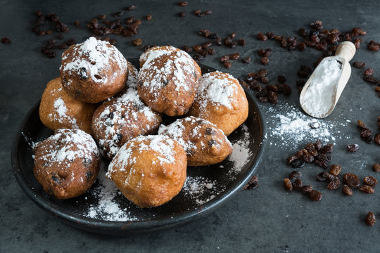 Oil dumplings (oliebollen) on black plate. Traditional treat on New Years Eve in The Netherlands