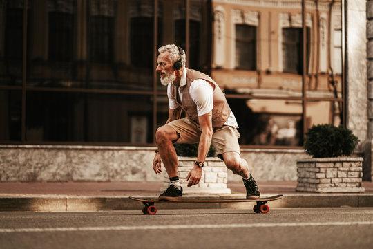 Portrait of bearded hipster man in white shirt on city street. Stylish happy model ride on longboard near road on buildings background