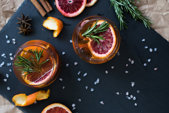 Negroni cocktail on black background served with a slice of orange and rosemary. Old cocktail classics. Italian aperitivo. Flatlay