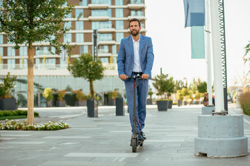 Young businessman in a suit riding an electric scooter