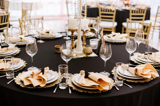A black tablecloth, expensive utensils and gold details decorate the wedding table