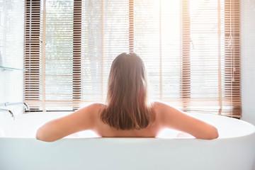 women wellness spa relaxing soaking in warm water bathtub of hotel suite.