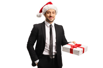 Young handsome man in a suit with a christmas hat holding a present