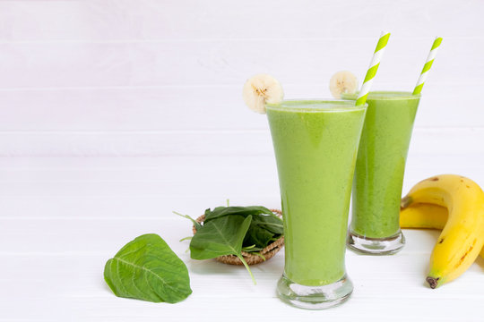 Banana mix spinach avocado apple smoothie green juice beverage healthy the taste yummy in glass drink episode morning on a  white wooden background.