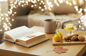hygge and cozy home concept - book, autumn leaves, cup of tea with lemon, almond nuts and oatmeal...