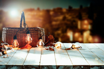 White wooden table background with brown basket and light bulbs. Blurred background and empty space for text decoration.