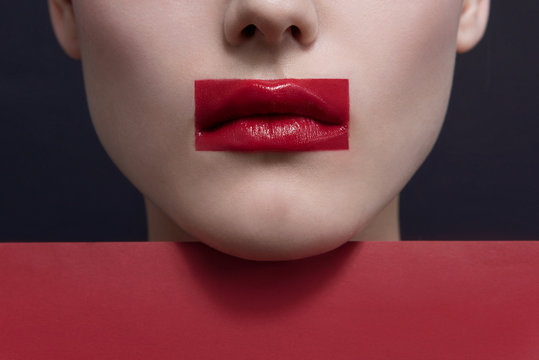 Close up, young woman lips with avant garde fashion art makeup. Red lips