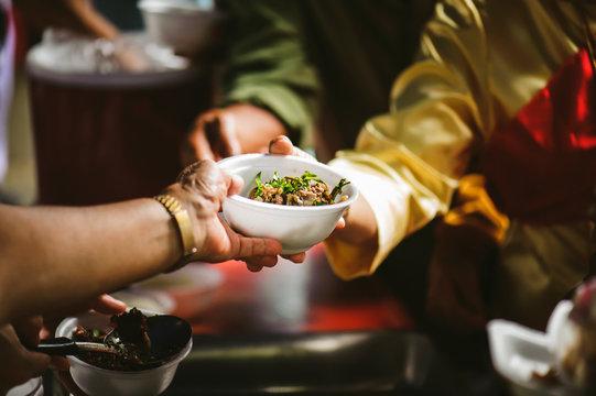 Volunteers serving food for poor people : concept of free food serving
