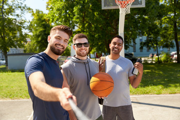 sport, leisure games and male friendship concept - group of happy men or friends taking picture by selfie stick on outdoor basketball playground