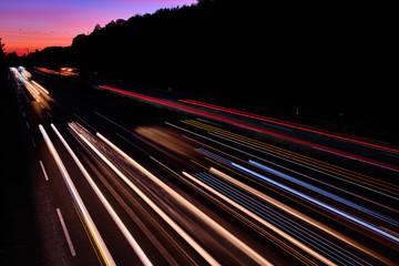Auto Lichtspuren. Lichter auf der Autobahn. Spuren von Autos. Abstraktes Licht, Lichtschweife. Autbahn bei Sonnenuntergang und viel Verkehr. Autobahn bei Nacht.