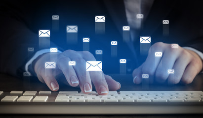 Business woman typing on keyboard with mail icons around