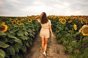 Poster Zonnebloem Beautiful young woman walking through sunflower field