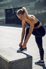 Beautiful woman in black sportswear tied the rope, prepare jogging