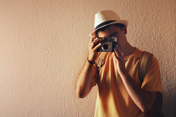 Man with a hat taking a picture with his camera.