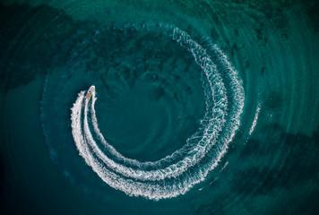Aerial view of speedboat creating wheel shape