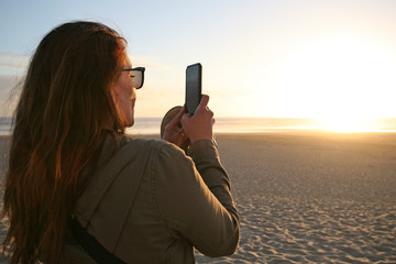 Young caucasian woman taking a photo of the ocean at sunset beachside