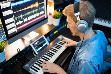Contemporary musician in headphones recording new music and songs in studio