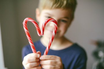 Playful boy making mustache with candy canes at home