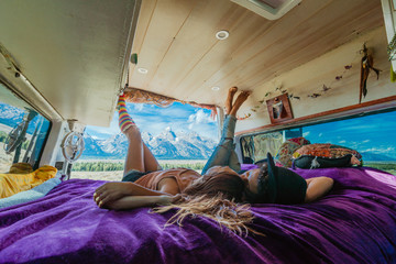 Interior view of a couple relaxing on their bed in a camper van