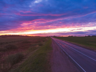 Fond de hotte en verre imprimé Prune Road at sunset. Paved country road with beautiful sky.Aerial shooting with drone.