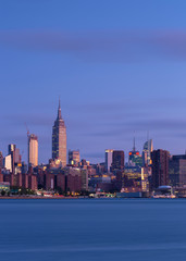 Midtown Manhattan with Empire State Building from East River at sunrise with long exposure
