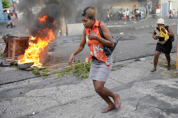 Women run past a burning barricade during a demonstration to protest against the shortage of fuel and against the government, in Port-au-Prince, Haiti