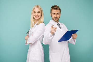 Happy medical team of doctors, man pointing to camera and smiling woman