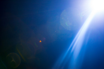 Flash of a distant abstract star. Abstract sun flare. The lens flare is subject to digital correction.