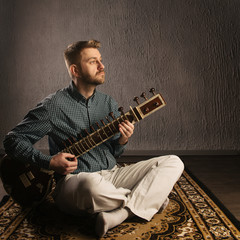 Portrait of a European man playing the sitar sitting on the carpet