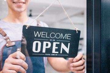 Young startup coffee cafe owener open and welcome customer.