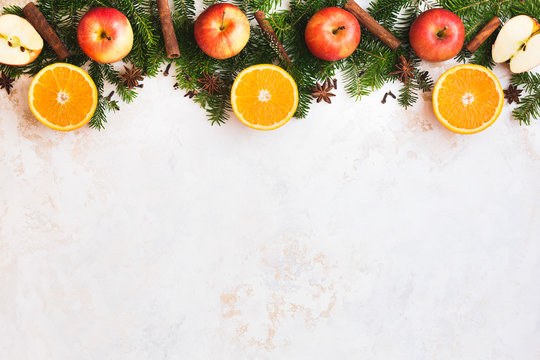 Christmas fresh  fruit abstract background border with orange half, spices, apple whole and half and natural fir tree over golden white rustic surface, top view