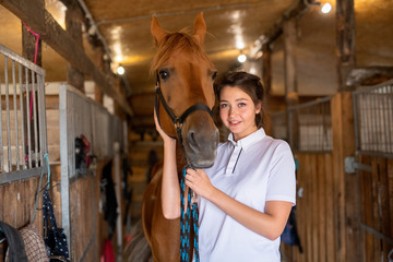 Pretty young smiling brunette keeping one hand by muzzle of purebred brown mare