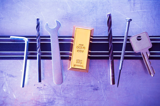 Tools and imitated gold bar on magnet board