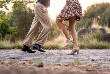 Two adult dancers feet dancing swing music outdoors in the park - unrecognizable people