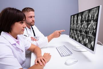 Doctors Looking At An MRI Scan At Computer