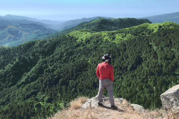 Hiker With Hat Looking Down On Trees Covered Mountains