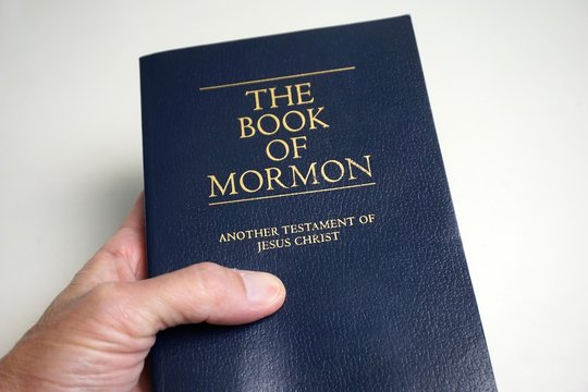 Person holding The Book of Mormon