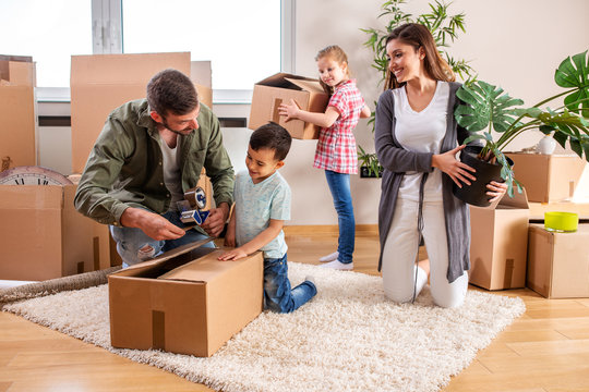 Young couple moving in a new home with their children helping them