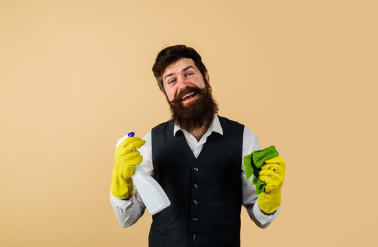 Male janitor with cleaning equipments. Bearded man in uniform, rubber gloves with cleaning products. Domestic service cleaner man with rag and cleaner spray. Professional cleaning man in uniform.