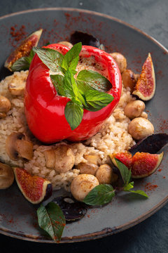 Risotto with mushrooms, figs and sweet pepper stuffed with meat and cheese. Meat dish.