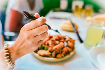Hand holding a  fork. A female hand is trying to use fork to eat. Focus on hand and fork - Image