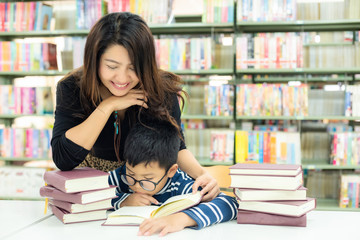 Schoolboy reading books for education and go to school with the guidance of her teacher in library...