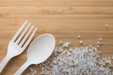 Fototapeta Biodegradable plastic pellets, spoon and fork made from starch and renewable sources obraz