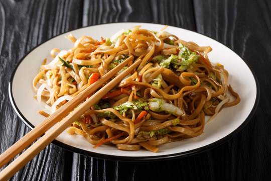 Classic Chinese fried chow mein noodles with vegetables close-up on a plate. horizontal
