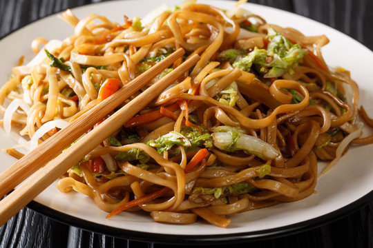Homemade fried chow mein noodles with Chinese vegetables close-up on a plate on the table. horizontal