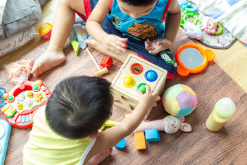 Group of children playing together with wooden toy box