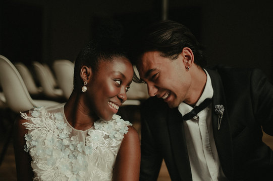 Bride and groom hug each other. Interracial marriage. Asian bride and groom.