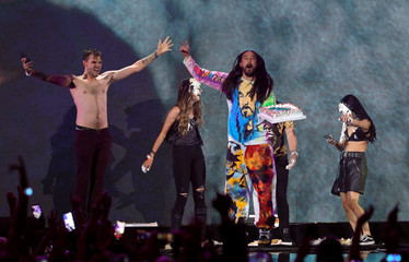 DJ Steve Aoki (C) throws cake into people's faces during the iHeartRadio Music Festival at T-Mobile Arena in Las Vegas